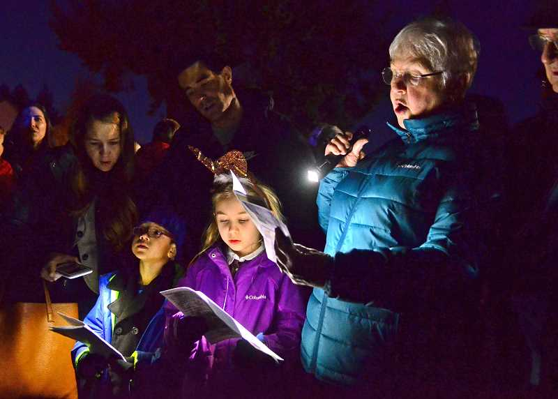 STAFF PHOTOS: VERN UYETAKE  - From right, Lynne Bacon, Grace and William Espinoza sing along with members of the Lake Oswego High School choir at Fridays tree lighting event.