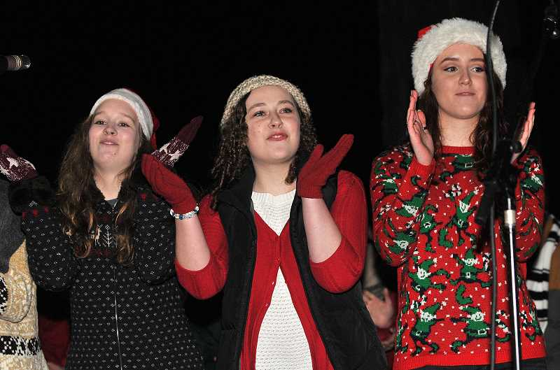 Lakeridge Company members , from left, Sarah Deyoung, Anne Wasman and Alex Lyon perform carols for the crowd at Millenium Plaza Park.
