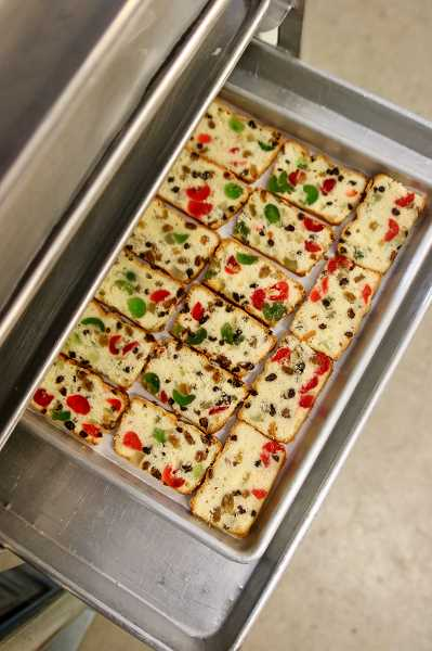 After the fruitcake is baked in loaf pans, it is sliced and toasted, which gives a crunchy texture when mixed in the ice cream.