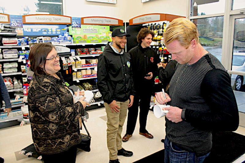 OUTLOOK PHOTO: STEVEN BROWN - Robyne Dodge Little, left, manager of Columbia Bank (Gresham branch), gets an autograph from Seattle Seahawks punter Jon Ryan during a Gresham Chamber of Commerce Try Local Tuesday event at Sherwin Williams on Northeast 223rd Avenue.