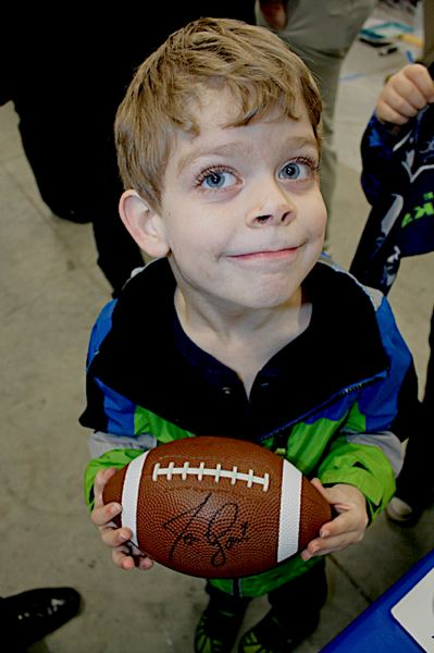 OUTLOOK PHOTO: STEVEN BROWN - Grant Hendrickson, 8, holds a football autographed by Seattle Seahawks punter Jon Ryan. Grant attended the event with his father, Rob Hendrickson, and brother Austin, 5.
