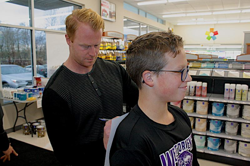 OUTLOOK PHOTO: STEVEN BROWN - Seattle Seahawks punter Jon Ryan signs an autograph for Harrison Kissinger, 13, a student at West Orient Middle School. Autograph gatherings were held Tuesday, Nov. 28, at Sherwin-Williams and Crunch Fitness on Northeast 223rd Avenue, Gresham.