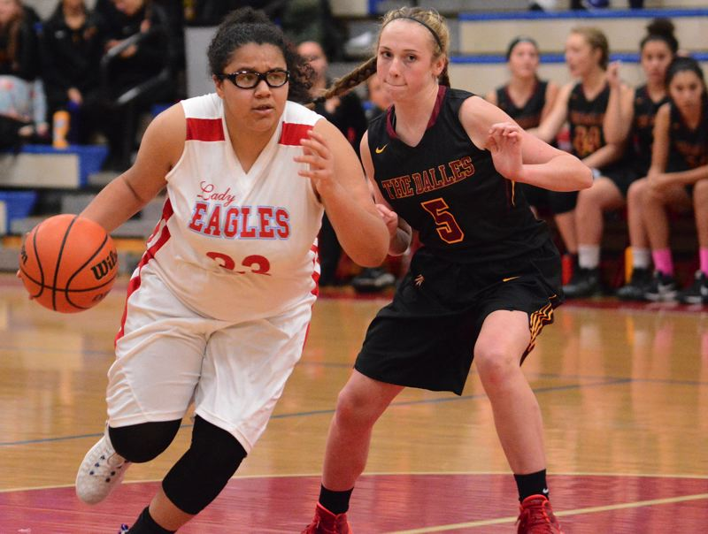 OUTLOOK PHOTO: DAVID BALL - Centennial point guard Dominique Andrews dribbles past The Dalles defender Jenna Miller during the Riverhawks' 43-38 win Wednesday night.