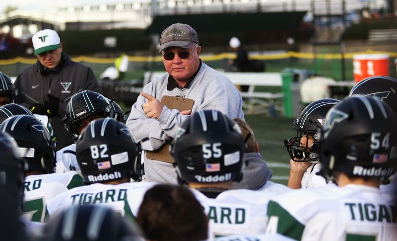 DAN BROOD - Tigard coach Craig Ruecker talks to the Tigers after the first half ended in Friday's Class 6A state playoff semifinal game.