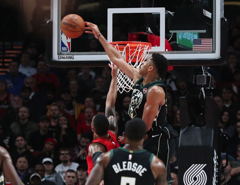 TRIBUNE PHOTO: JAIME VALDEZ - Giannis Antetokounmpo of the Milwaukee Bucks blocks a shot by Trail Blazers guard Damian Lillard.