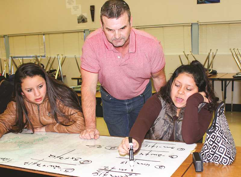 HOLLY SCHOLZ - Crook County Middle School seventh-grade math teacher Jim Crouch instructs Karina Lopez, left, and Giana Robles on a math lesson during the English Language Learners After-School Math Tutorial.