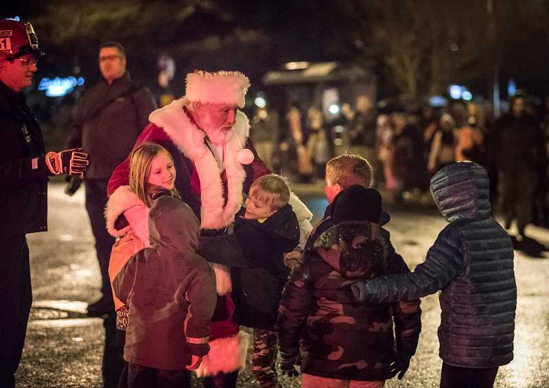 TIMES PHOTO: JONATHAN HOUSE - Santa Claus is greeted by children as he arrives at the Downtown Tigard Holiday Tree Lighting.