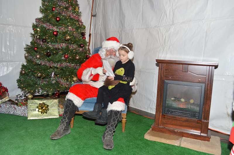 GAZETTE PHOTO: RAY PITZ - Abigail Harry, 5, reads to Santa from a list of items shed like for Christmas during festivities at the Robin Hood Holiday Festival. With her is Timothy the Turtle, a stuffed animal who accompanies children during their many adventures in Mrs. Jordans kindergarten class at Archer Glen Elementary School.