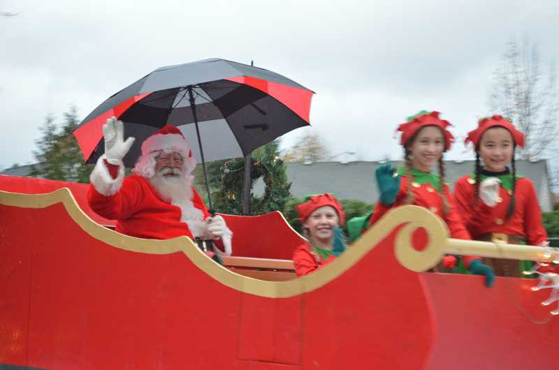GAZETTE PHOTO: RAY PITZ - Santa and his elves wave as from a float as they make their way down Sherwood Boulevard Dec. 2.