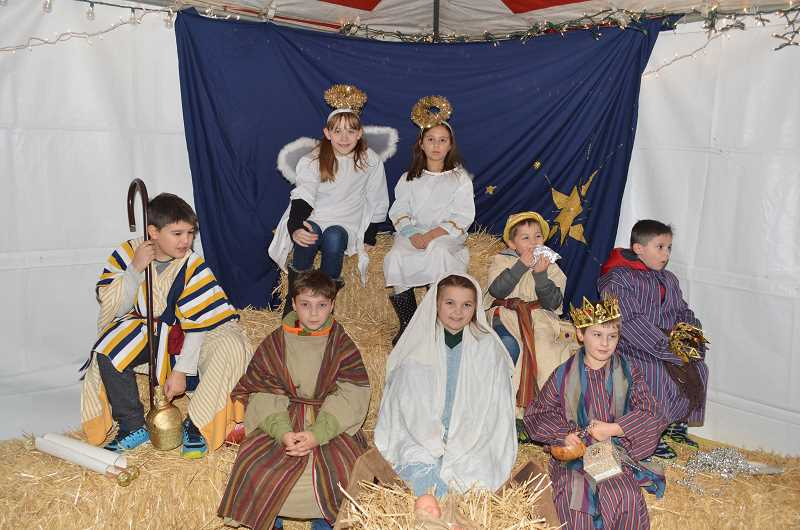 GAZETTE PHOTO: RAY PITZ - Children from St. Pauls Lutheran Church create a live Nativity scene inside a tent at Cannery Square Plaza.