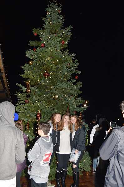 GAZETTE PHOTO: RAY PITZ - Three girls pose as a friend snaps a photo in front of the Christas tree at Cannery Square Plaza Dec. 2
