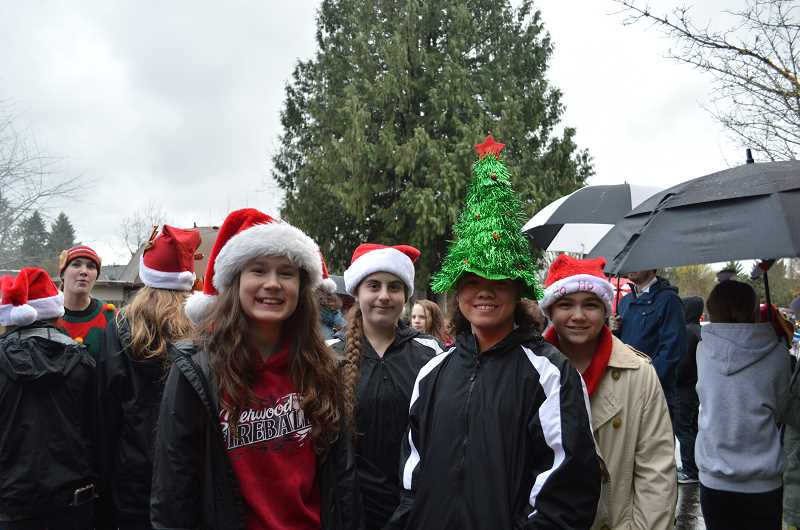 GAZETTE PHOTO: RAY PITZ - Members of the Fireballs softball team pose for a photo before boarding a float in the Robin Hood Holiday Festival parade.