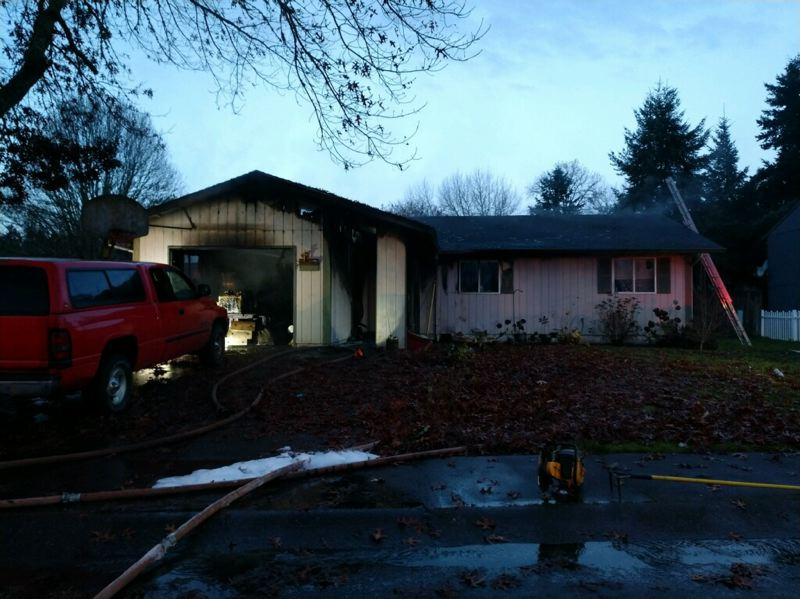 PHOTO COURTESY OF SCAPPOOSE FIRE DISTRICT - Fire crews respond to a fire that started in an attached garage of a home in Scappoose Sunday morning. The fire displaced five people.