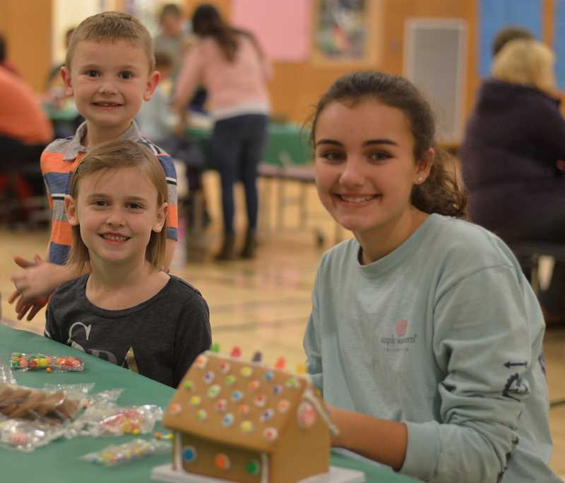 SPOKESMAN PHOTO: CLARA HOWELL - Alexis, 13, (right), Ainsley, 7, (middle) and Boston Hagler, 5, (left) enjoy family time celebrating the holiday season at Boones Ferry.