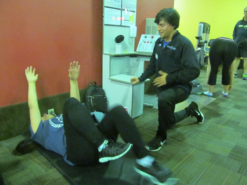 PHOTO BY DICK TRTEK - James Hodgson, health promotions director at East Side Athletic Club, works with one of the participants in the Fit4Me program during a recent training session.