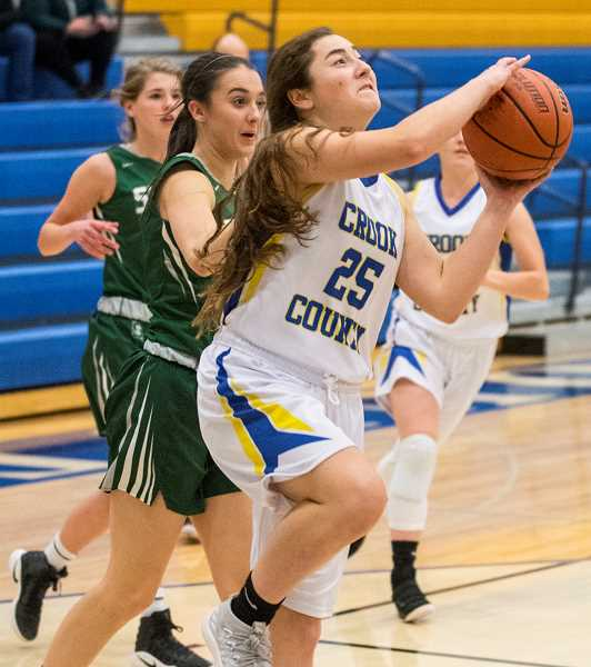 LON AUSTIN/CENTRAL OREGONIAN - Emma Ackley goes to the hoop for two of her six points during the Cowgirls one-point loss to the Sisters Outlaws last Friday.