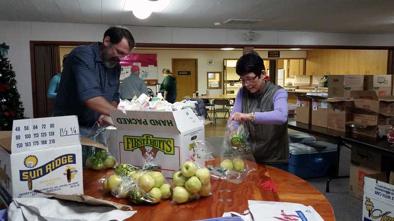 COURTESY PHOTO - Volunteers pack apples for the Christmas boxes given to those in need in the Banks community.