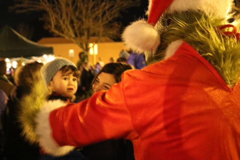 OUTLOOK PHOTO: ZANE SPARLING - Isaiah Farrouge, 17 months, puts on a brave face while meeting with the Grinch on Friday, Dec. 1. Mom Shannon Farrouge said it was their first time attending the annual tree lighting ceremony.