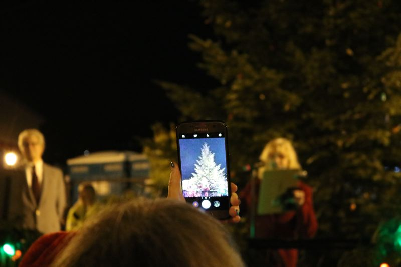 OUTLOOK PHOTO: ZANE SPARLING - A woman takes a cellphone picture of Troutdale's Christmas tree before the annual tree lighting.