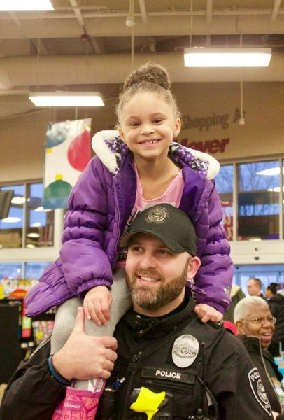OUTLOOK PHOTO: CHRISTOPHER KEIZUR - Officer Jon Buck gives a child a ride during 'Shop with a Cop,' an event that helps get Christmas gifts to local children.