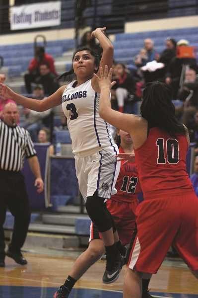 PHIL HAWKINS - Woodburn sophomore Lina Cabrera lofts a shot over the North Salem defense in the Bulldogs' 61-43 loss in Friday's season opener. Cabrera is one of six new members to the Woodburn girls basketball varsity program this year.
