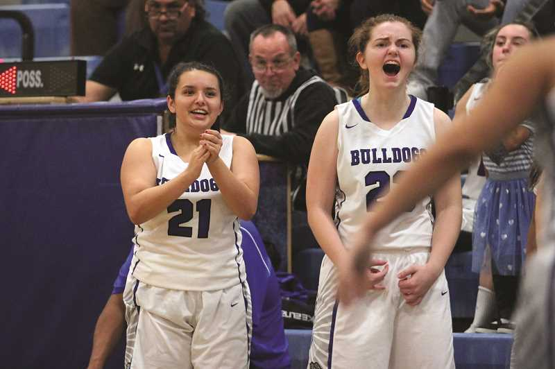 PHIL HAWKINS - Varsity newcomers Jasmine Mendez (left) and Jordan Mann cheer from the bench in the second half of Woodburn's season opener against North Salem on Friday.