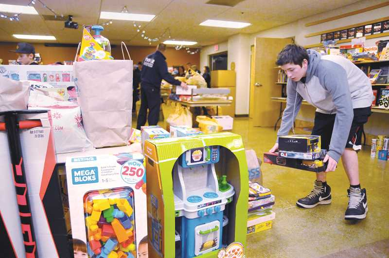 GARY ALLEN - Members of the Bowlby family and others drop off hundreds of toys Friday evening at the main fire station in Newberg.