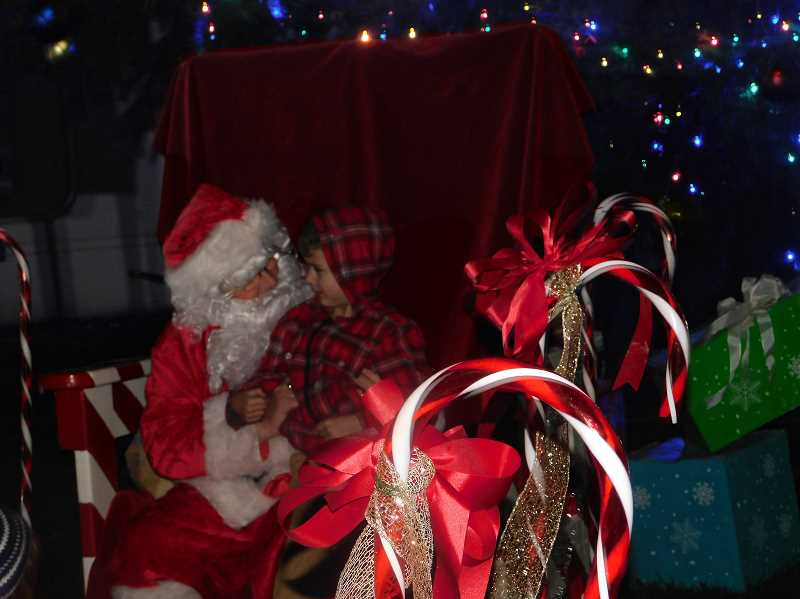 ESTACADA NEWS PHOTO: EMILY LINDSTRAND - Santa visits with a young friend during the city of Estacada's Christmas tree lighting event.