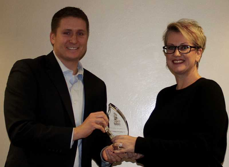 THE TIMES: MANDY FEDER-SAWYER - Marketplace Manager for the Better Business Bureau, Northwest, Stephen Mayer presents the Better Business Bureau Torch Award to Carey Flamer-Powell.