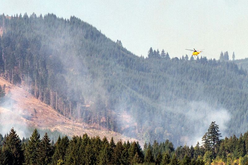 FILE - Firefighting helicopters take water to dump from Hagg Lake to dump on the Scoggins Creek Fire in 2014.