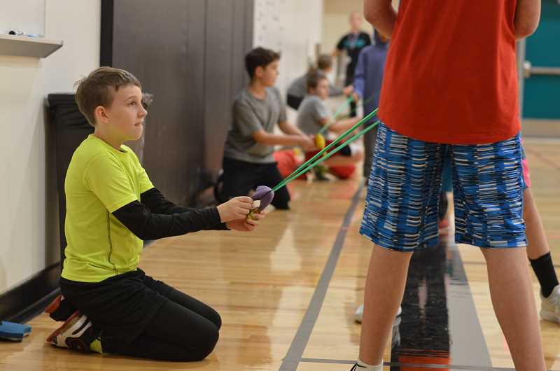 SPOKESMAN PHOTO: CLARA HOWELL - Sixth-grader Rock Ward works with his team to fling the rubber chicken into the bucket.