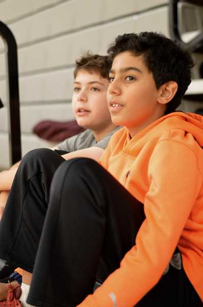 SPOKESMAN PHOTO: CLARA HOWELL - Sixth-graders Aric Mistovich (left) and Nour El Din Shahaeen (right) cheer on their parents during game night.