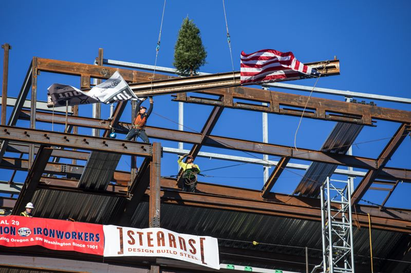 PAMPLIN MEDIA GROUP: JON HOUSE - A construction worker grabs the last beam during a topoff ceremony for the new Multnomah County Health Department Headquarters.