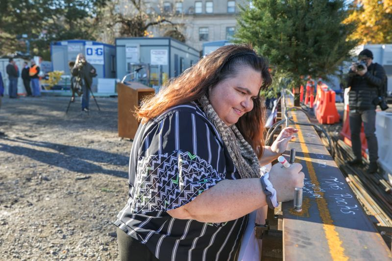 PAMPLIN MEDIA GROUP: JON HOUSE - Multnomah County Health Department client Wendy Shumway signs the last beam before the start of a topoff ceremony for the new headquarters.