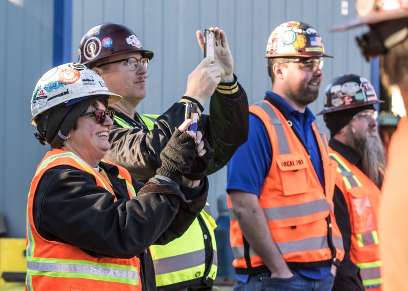 PAMPLIN MEDIA GROUP: JON HOUSE - Construction workers record the raising of the last beam during the topoff ceremony for the new Multnomah County Health Department Headquarters.
