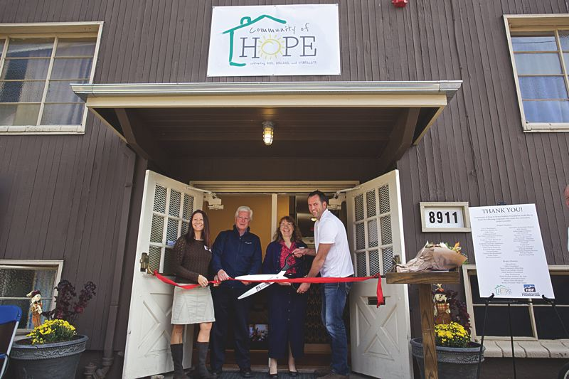 PORTLAND TRIBUNE: JAIME VALDEZ - Cutting the ribbon at the opening of the Community of Hope were (from left): Brenda Ketah, project manager for Home Builders Foundation; Ken Cowdery, executive director of the Home Builders Foundation; Linda Jo Devlaeminck, director of the family shelter in St. Johns; and Dale Hosley, president/owner of Clear Water Construction Services, who served as general contractor.