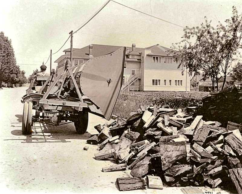 COURTESY OF SMILE HISTORY COMMITTEE - This 1920 photo shows a delivery of slab wood to the street in front of a home which had ordered it. The Eastside Lumber Mill delivered such left-over chunks and pieces of wood from their mill. The editor of THE BEE at this time wrote some critical comments about Sellwood residents who left heaps of firewood at the curb for weeks on end. This photo looks east on Spokane Street, with the Sellwood Community Center - now on the Historic Register, and still on the corner of S.E. 15th - in the background.