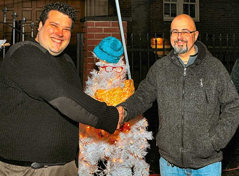 DAVID F. ASHTON - Outgoing FABA President Matthew Micetic, owner of Red Castle Games, greeted incoming president Allen Rowand of Gray Dog Digital, in front of Twiggy the Traveling Winter Tree.