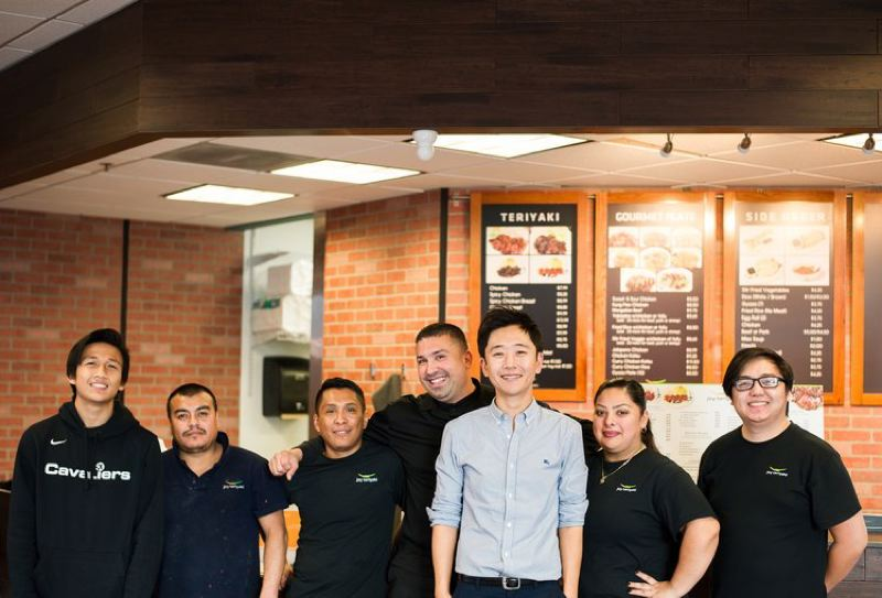 CONTRIBUTED - Justin Hwang poses with employees of his Joy Teriyaki chain, which was started by his parents in Seattle.
