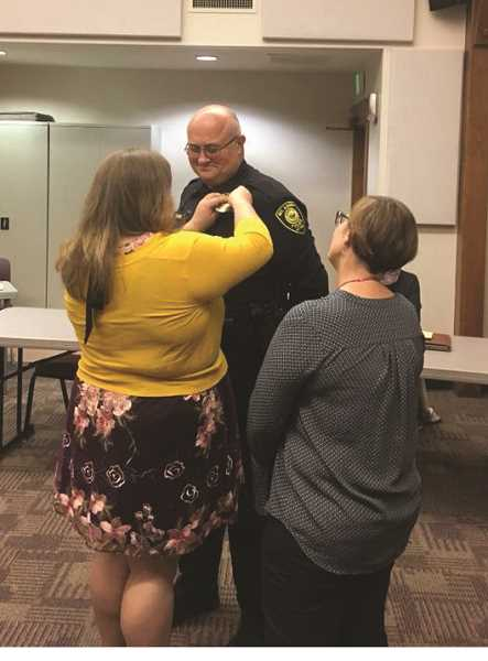 COURTESY PHOTO: CITY OF MOUNT ANGEL - Mount Angel's new chief of police was sworn in on Dec. 4 at the city council meeting. His wife and daughter pinned his badge to his uniform at the ceremony.