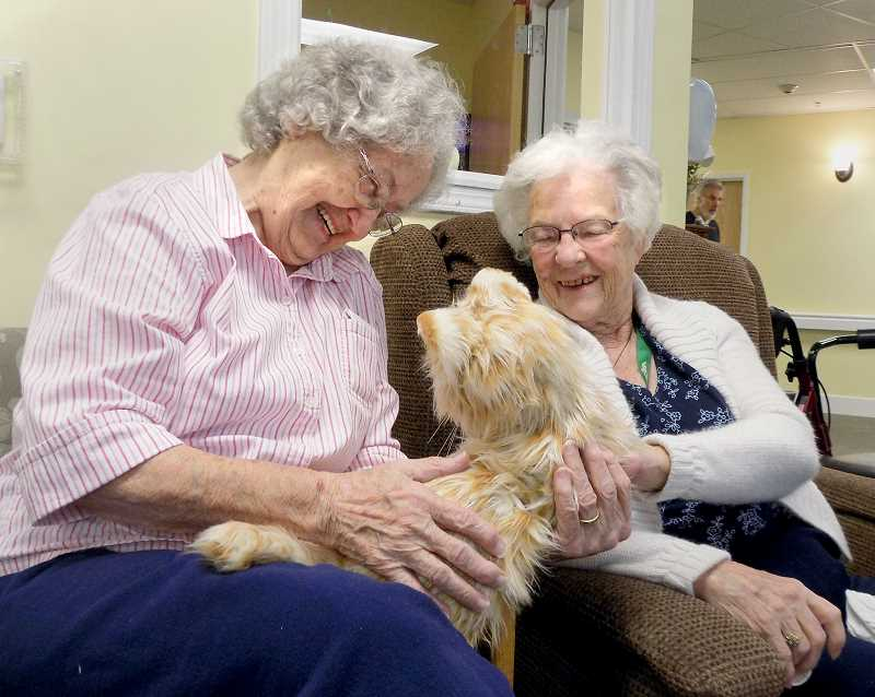 PMG PHOTO - A pair of local memory care residents spend time with Cuddles, a robotic cat that a Sherwood woman takes on visits to facilities in the area.