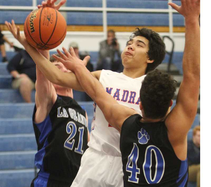 WILL DENNER/MADRAS PIONEER - Cash Reese (middle) draws a foul in traffic against La Grande on Saturday. Reese has reached double figures in scoring in two of three games, as have Kanim Smith and Byron Patt (not pictured).