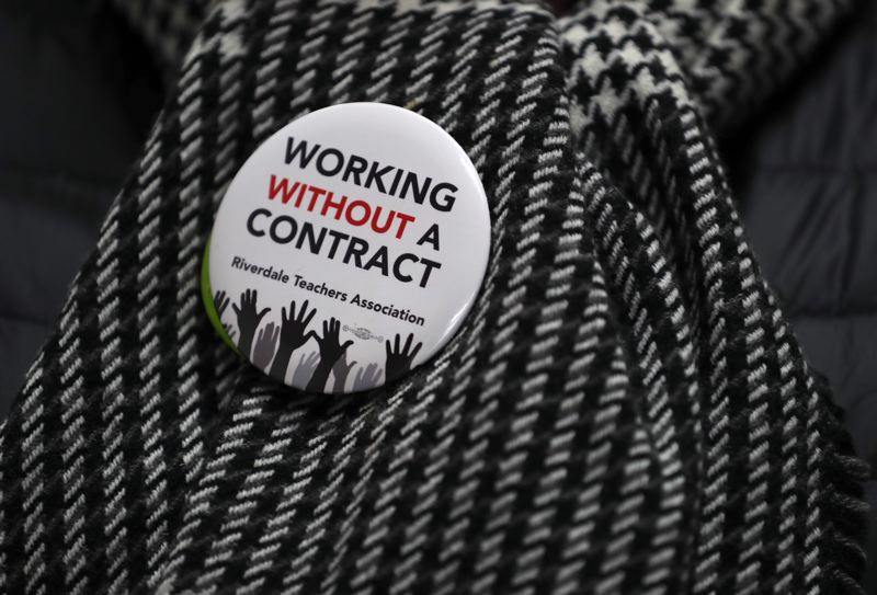 TRIBUNE PHOTO: JAIME VALDEZ - Riverdale teachers wear buttons to show that they are working without a contract.