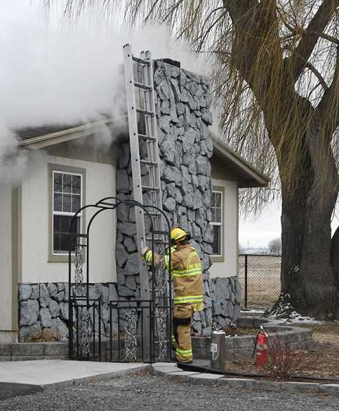 LINDA LARSON - A firefighter prepares to attack fire on the roof of a house on Southwest Highway 97 on Dec. 10.