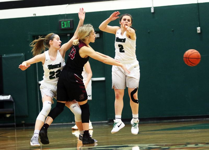 DAN BROOD - Sherwood senior Lauren Scarvie (center) passes the ball past Tigard sophomores Delaney Leavitt (left) and Kennedy Brown in Monday's game.