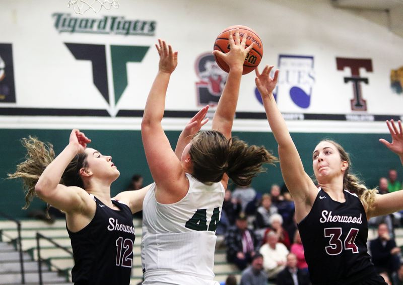 DAN BROOD - From left, Sherwood's Kaytlin Cooke, Tigard's Dani Lyons and Sherwood's Cali Etherington battle for the ball during Monday's game.