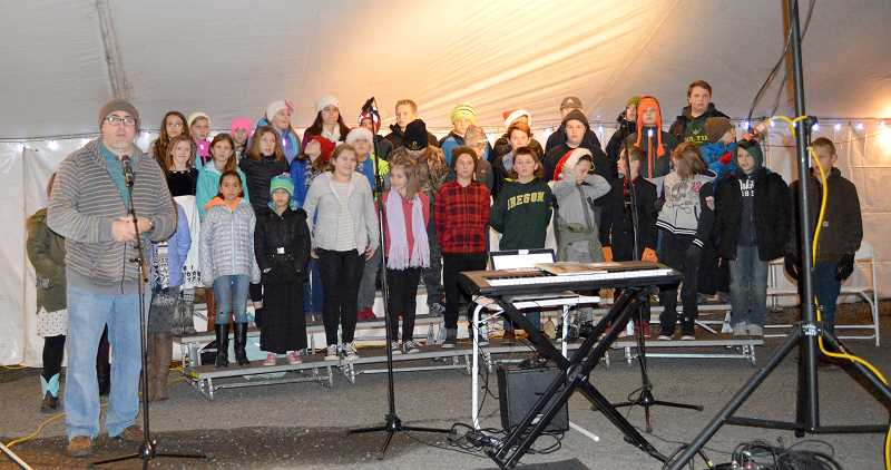 PIONEER PHOTO: CINDY FAMA - The fifth grade choir performs under the direction of Bobby Rice at the tree lighting Thursday.