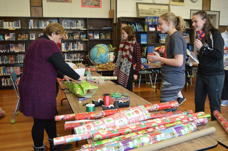 SPOTLIGHT PHOTO: NICOLE THILL - Donna Spitz, left, helps wrap gifts for Jaedyn Maller and Kaitlin Dahla during the Scappoose Middle School Holiday Feather Bazaar on Tuesday, Dec. 12. Spitz, who is librarian' Cindy Krieck's sister, also donated 60 hand-made crochet hats and beanies for the bazaar,