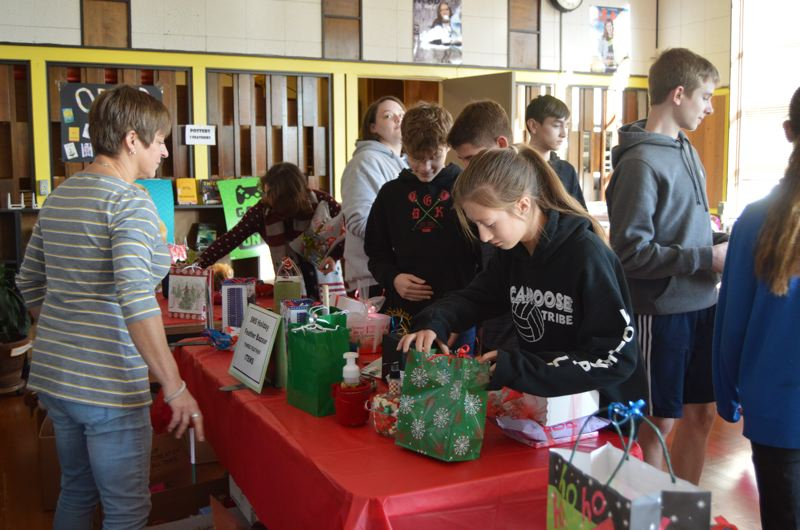 SPOTLIGHT PHOTO: NICOLE THILL - Volunteer Gail Sykes, left, monitors gift tables while a group of students peruse the selection of items available to purchase. Students were able to choose from dozens of items at varying prices.