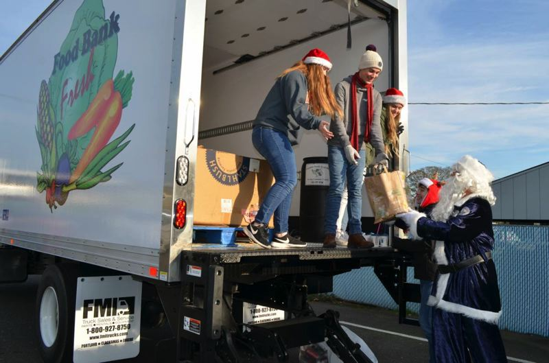 PHOTO COURTESY OF THE ST. HELENS POLICE DEPARTMENT - Santa Claus helps volunteers load food donations into a delivery truck at the St. Helens Police Department during its annual Donut Day fundraiser. The police department collected more than $2,000 and 3,700 pounds of donated food items to benefit the Columbia Pacific Food Bank.
